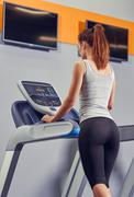 Woman Running On Treadmill At Gym Stock Photos