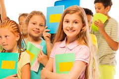Girl with textbook in large group of children - stock photo