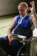 Quad rugby player bandaging his arm Stock Photos