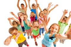 Cheering kids lifting hands up in air - stock photo