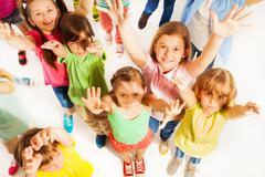 Bunch of kids lifting hands in the air - stock photo