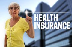 health insurance touchscreen is shown by senior - stock photo