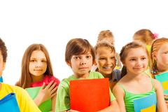 Calm kids standing with textbooks - stock photo
