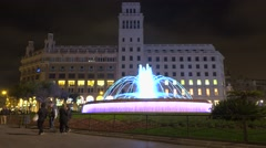 Catalonia Square bright illuminated fountain at night, people pass at foreground Stock Footage