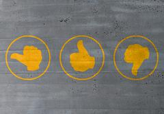 thumb valuation icons on cement concept - stock photo