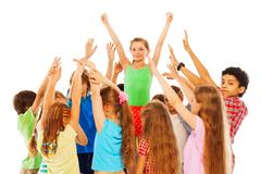 Happy girl with raised hands in group of kids Stock Photos