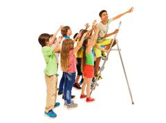 Group of kids trying to be first on ladder - stock photo