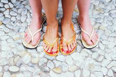 Feet in flip flops Stock Photos