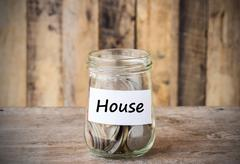 Coins in glass money jar with house label, financial concept. Stock Photos