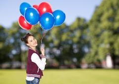 Stock Photo of happy teenage girl with helium balloons