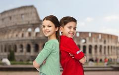 happy boy and girl standing over coliseum in rome - stock photo
