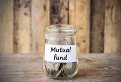 Coins in glass money jar with mutual fund label, financial concept. - stock photo