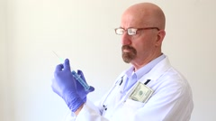 Doctor with a syringe and money in his pocket Stock Footage