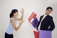 Woman throwing folders at man Kuvituskuvat
