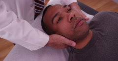 Good-looking black male having neck examined by chiropractor Stock Footage