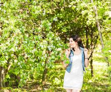 Spring woman in summer dress walking in green park enjoying the sun. Playful and - stock photo