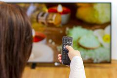 Girl holding tv remote control and surfing programs - stock photo