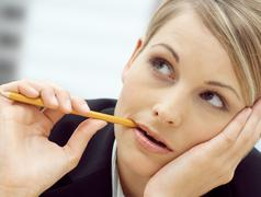 Woman chewing a pencil Stock Photos
