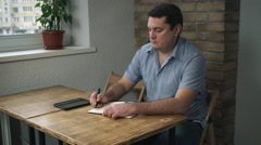 Adult male sitting in a cafe with a diary and a tablet, taking notes in a Stock Footage