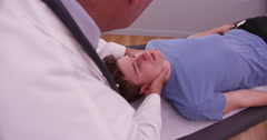 Mid aged chiropractor examining neck joint of young adult male - stock footage