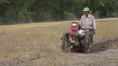 Farmer uses plowing machine on dry paddy field, failed harvest, poverty, Asia Stock Footage