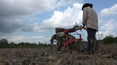 Poor farmer plowing dry rice paddy field in Vietnam, Southeast Asia Stock Footage