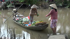 Grocery delivery in the Mekong Delta, woman sells fruit and vegetables by boat Stock Footage