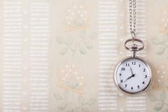 old pocket clock against of vintage wallpaper background - stock photo