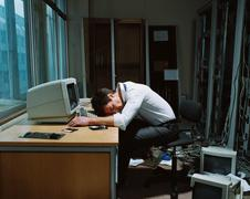 Office worker slumped on his desk - stock photo