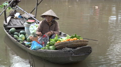 Woman sells fresh fruit and vegetables from a boat, Mekong Delta, Vietnam Stock Footage
