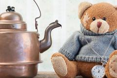 Teddy bear and copper kettle on background of old wallpaper - stock photo