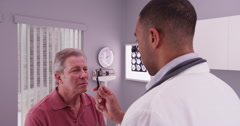 Elderly male patient with young doctor examining his concussion Stock Footage