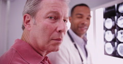 Senior male patient looking at camera with young medical practitioner Stock Footage