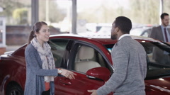 4K Excited couple in car dealership take key to new car from salesman Stock Footage