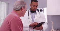 Middle aged male patient consulting with young doctor on a handheld tablet Stock Footage