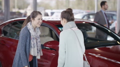 4K Female friends in car dealership take key to new car from salesman Arkistovideo