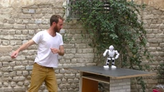 A humanoid robot teaches a young man to dance.  Stock Footage