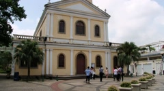 People stand in front of the church building of Taipa village in Macau, China. Stock Footage