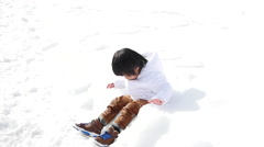 Asian boy in winter clothes playing with snow Stock Footage