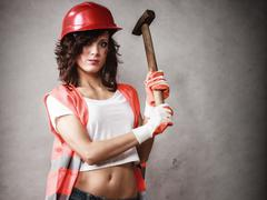 Sexy girl in safety helmet holding hammer tool - stock photo