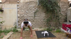 A humanoid robot and a young man exercise push ups Stock Footage
