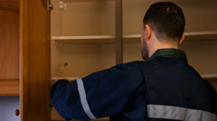 Man looking in cupboard for pest control Stock Footage