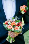 Groom holds a wedding flowers bouquet - stock photo
