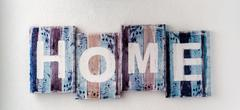 Handmade HOME sign, wooden colorful planks over white wall background. Rustic Stock Photos