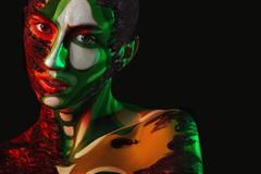 Woman with body art on face and clay in fashion image Stock Photos