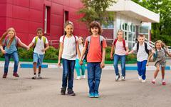 Rows of kids with rucksacks near school walking - stock photo