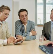 Three businessmen with a handheld computer Stock Photos