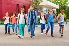 Children with rucksacks near school walking - stock photo