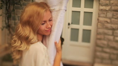 Fantastic blond bride tenderly holds her lace wedding dress Stock Footage