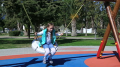 Portrait of a cute girl swinging at the playground - stock footage